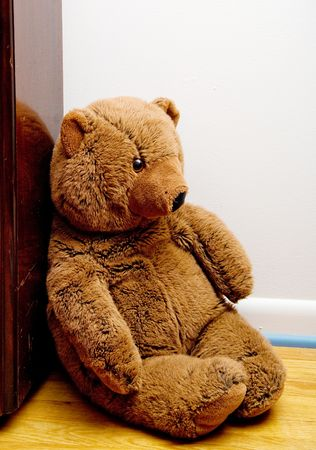 A teddy bear sitting in a corner.