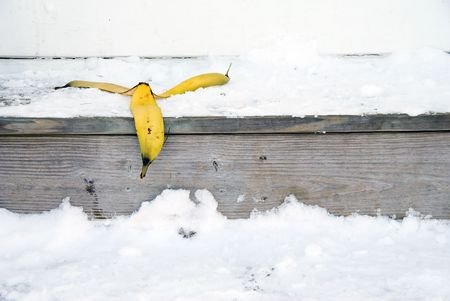 A banana peel on snow covered steps.