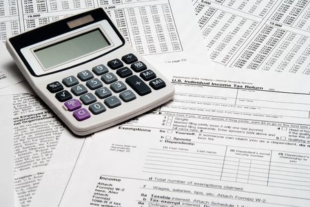 exemption: A calculator sitting on top of tax forms.