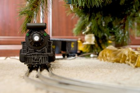 A model train on a track under a Christmas tree.