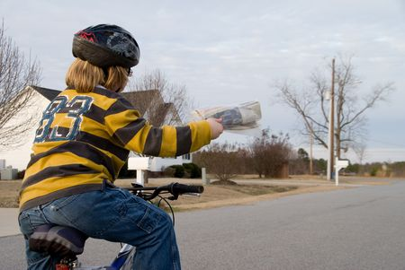 A boy delivering newspapers on his bicycle.
