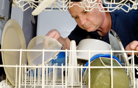 dirty man: A man loading or unloading a dishwasher. Stock Photo