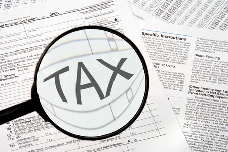 federal tax return: Federal tax forms under a magnifying glass. Stock Photo