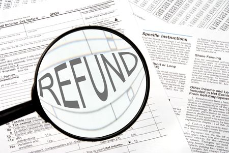 Federal tax forms under a magnifying glass. Stock Photo