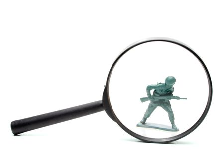 investigated: A toy soldier being investigated under a magnifying glass. Stock Photo