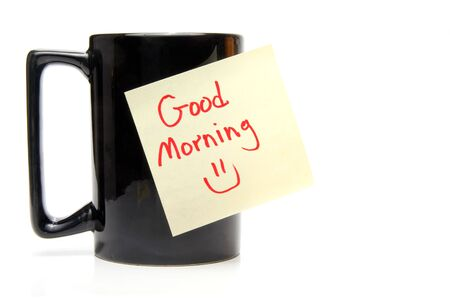 A coffee cup with a good morning sticky note. Imagens