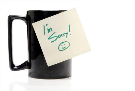 Una taza de café con una nota de Im Sorry.