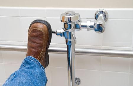 flushing: Flushing a Toilet with a foot in a restroom. Stock Photo
