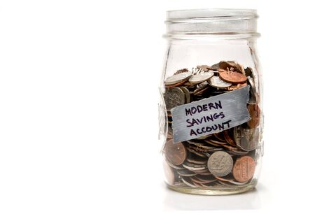 saved: Assorted coins being saved in a mason jar.