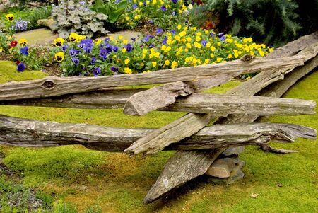 A split rail fence surrounding a floral garden. photo