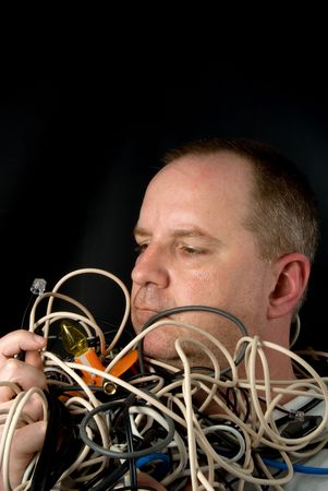 A man tangled up in wires and cables. Stock Photo - 4786395
