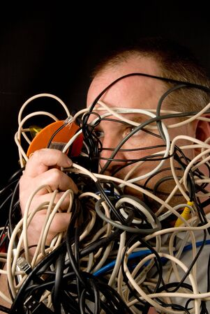 mess: A man tangled up in wires and cables. Stock Photo