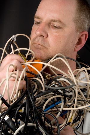 A man tangled up in wires and cables. Stock Photo - 4786397