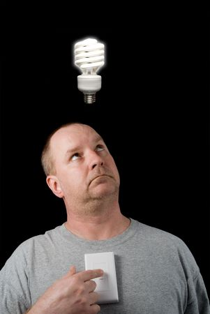 florescent light: A man looking at a lighted lightbulb over his head. Stock Photo