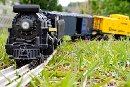 A toy train locomotive traveling across the country. photo