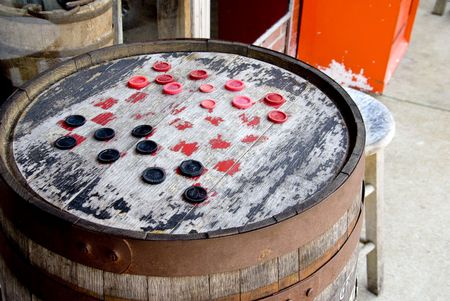 Checkers on a board made from an old barrel. Stock Photo - 4824712