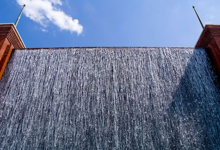 spewing: A man made waterfall spewing cold water on a hot day.