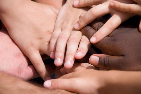 kids holding hands: A diverse pile of hands signifying togetherness.
