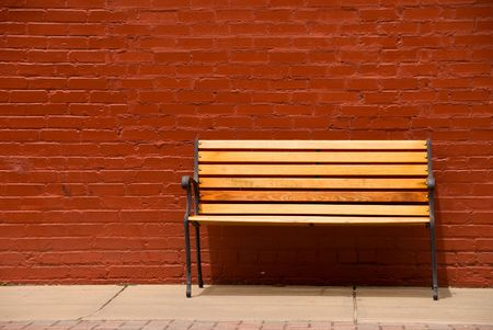 A bench beside a red brick wall. photo