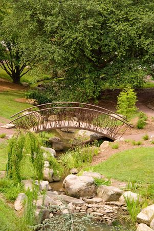 An asian style Arched Bridge in a garden. photo