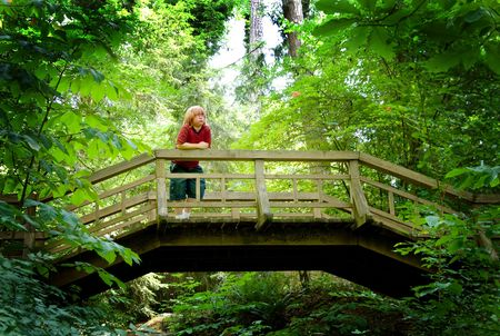 foot bridge: A young boy looking over the side of a fotbridge. Stock Photo