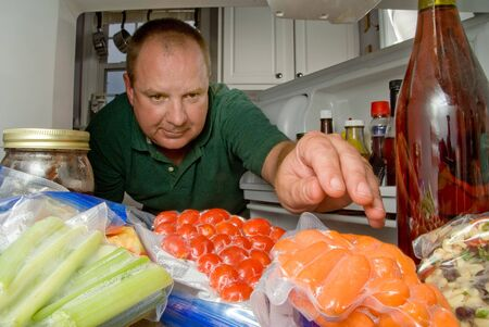 icebox: A man selecting various items from a modern refigerator. Stock Photo