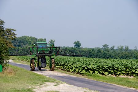 A large commercial crop spraying farm tractor. photo
