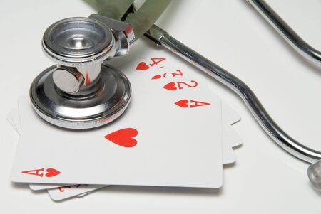 A Stethoscope and Hand of Hearts playing cards. photo