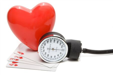 A Sphygmomanometer with some heart playing cards.
