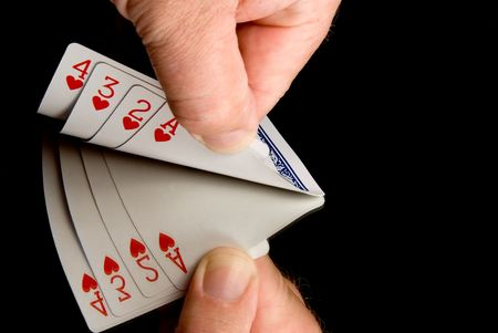 thier: A person peaking at thier hand of cards.