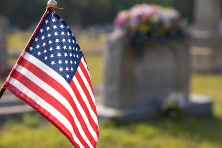 A flag at a grave in a cemetary.
