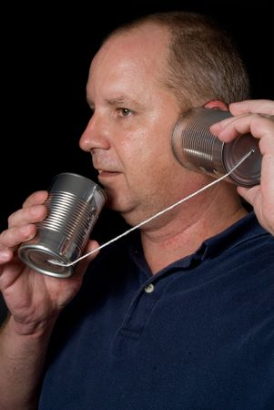 A man talking on a tin can phone.