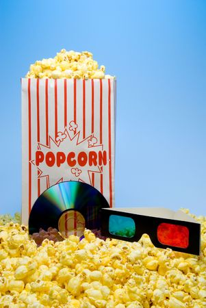 A DVD, 3D glasses and a bag of popcorn. photo