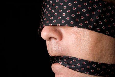 kokhalzen: Een man geblinddoekt en mond gesnoerd met een stropdas.