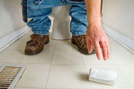 toilet: A man gropping for fallen toilet paper.