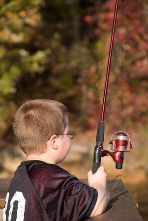 暖かい秋の日の湖で釣り少年。 写真素材