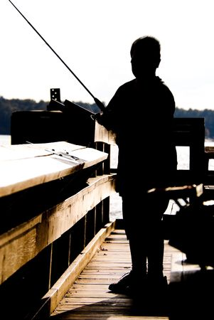 Silhouette of a boy fishing at a lake on a warm autumn day. photo