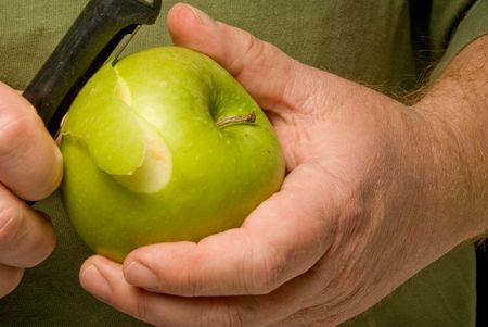peal: A person in the process of Peeling an Apple