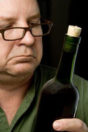 connaisseur: Un vino Connoisseur ispezionare una bottiglia di vino rosso.