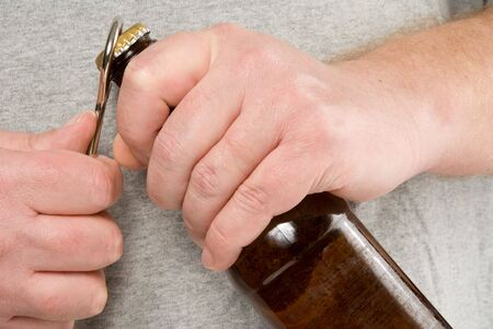 A person using a bottle opener to open a beer. Stock Photo - 6169367