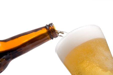 carbonation: Una persona pouring cerveza en un vaso de Pilsen. Foto de archivo