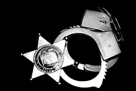 restraints: A sheriffs badge and a pair of handcuffs
