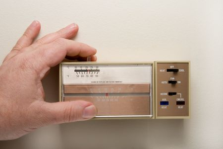 Setting a thermostat to cool in the summer. photo