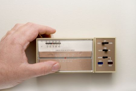 turn the dial: Setting a thermostat to heat in the winter.