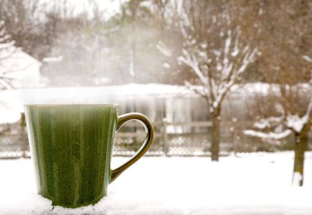 A cup of Steaming Coffee on a snowy morning
