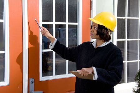 female construction worker: A female construction worker inspecting a building
