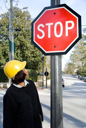 A female construction worker inspecting a stop sign. Stock Photo - 6505218