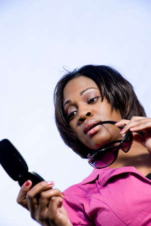 An African American woman reading a text message on the phone Stock Photo - 6505220