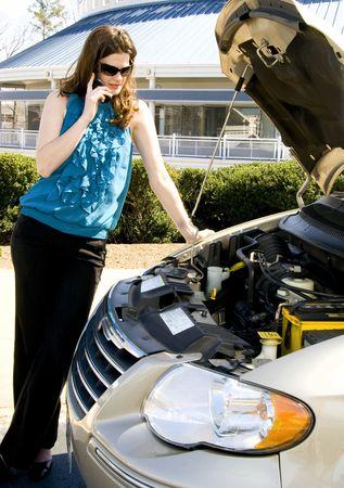 A beautiful young woman having car trouble photo