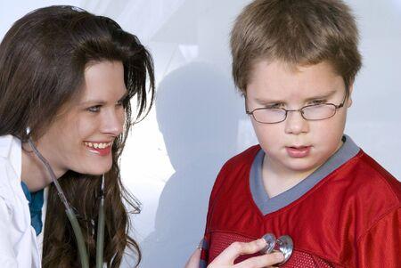 A Female Pediatrician examining a young boy photo